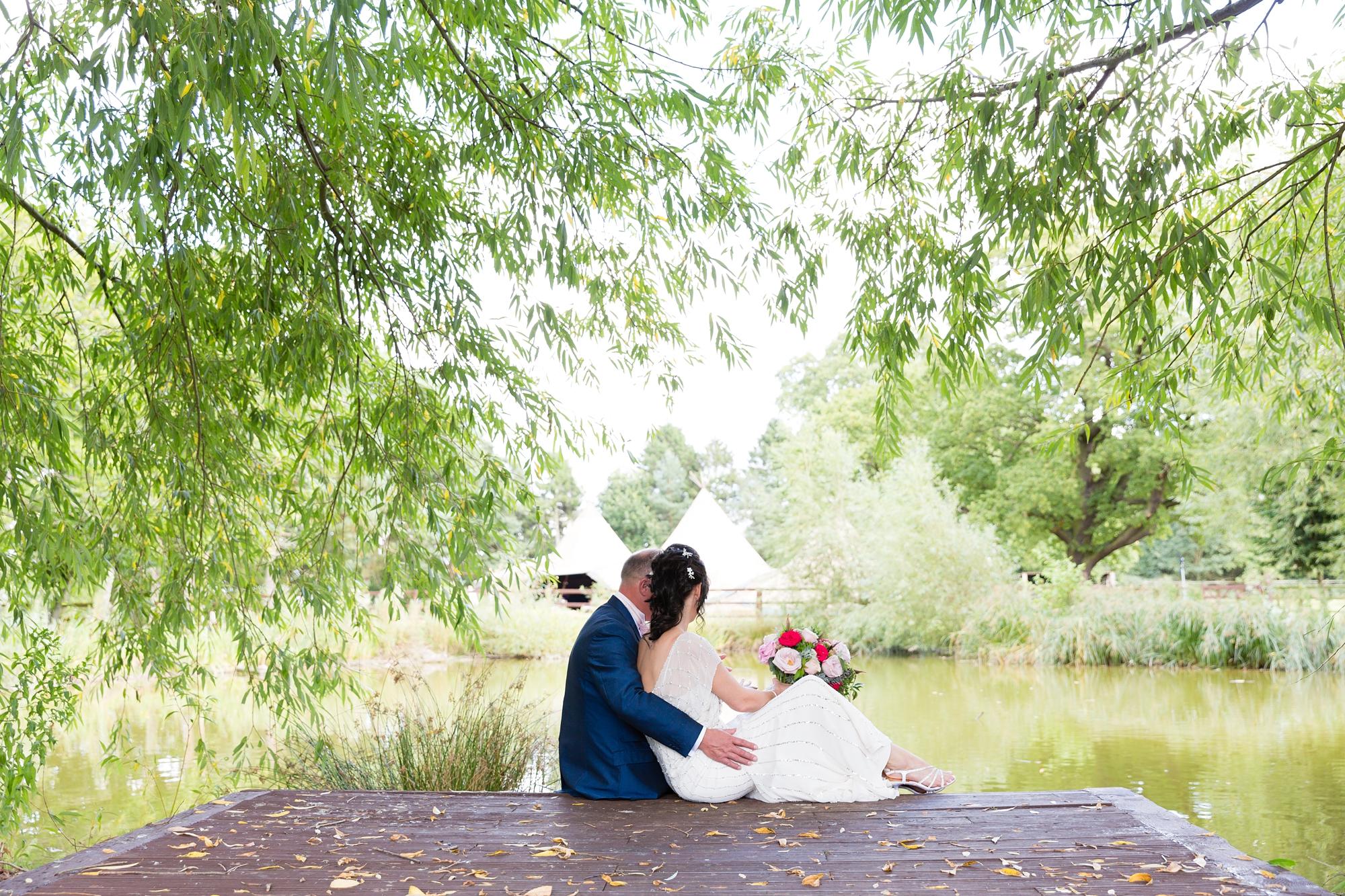 Villa Farm Weddings bride and groom sitting on jetty