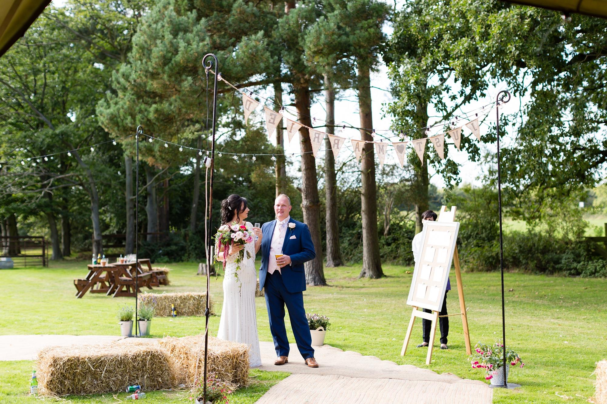 Villa Farm Weddings bride and groom walk up to tipi