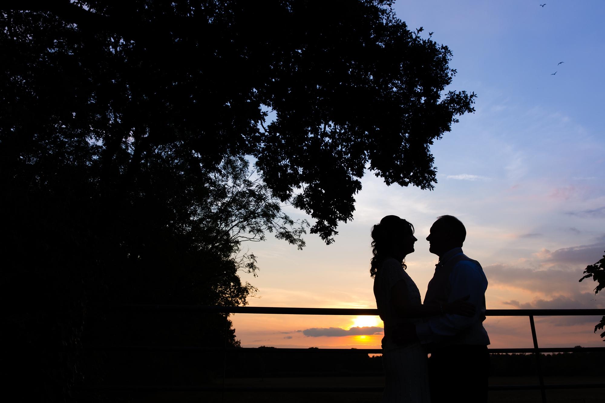 Bride & groom in silhouette by gate Villa Farm Weddings