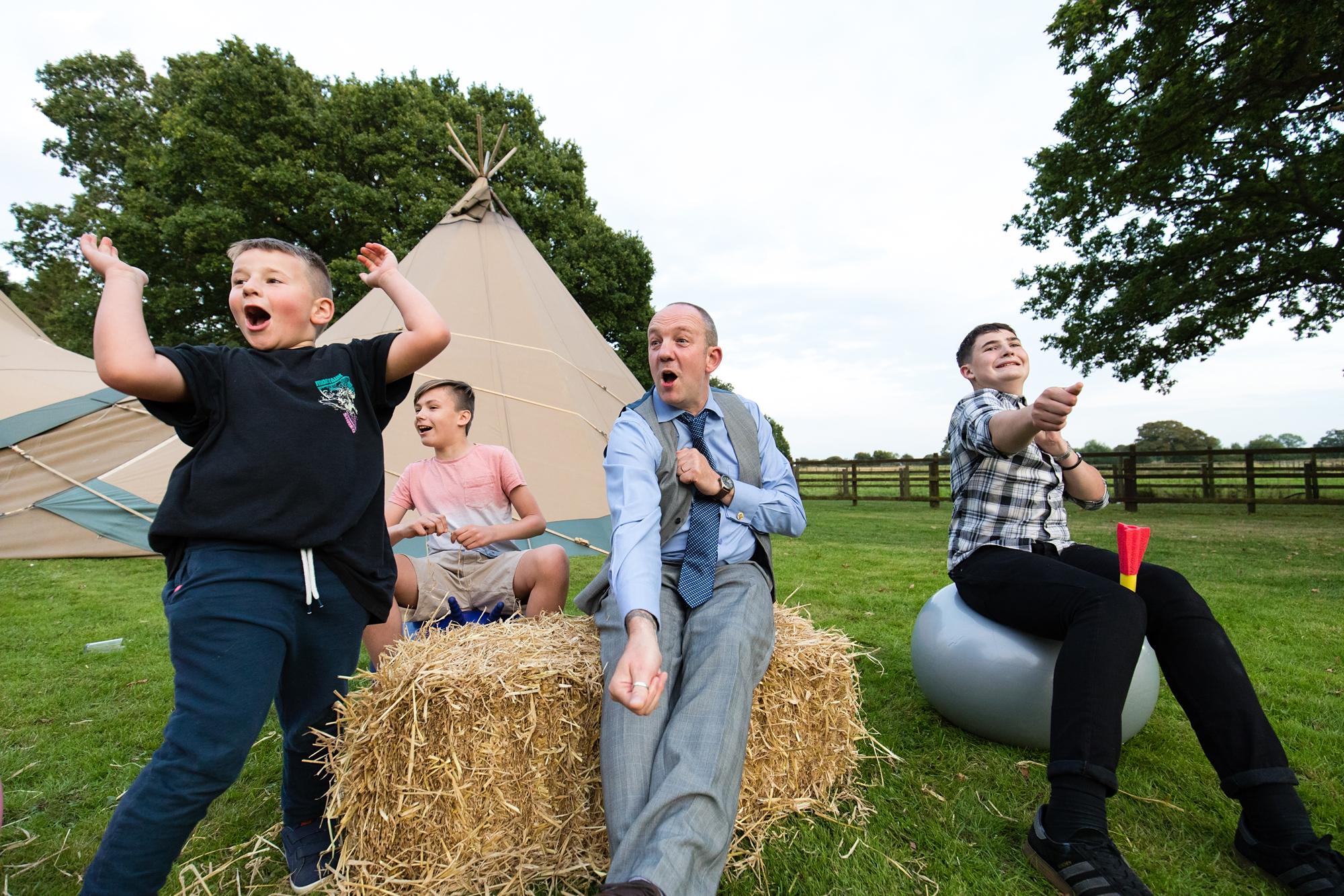 Villa Farm Weddings guests having fun sitting on hay bales