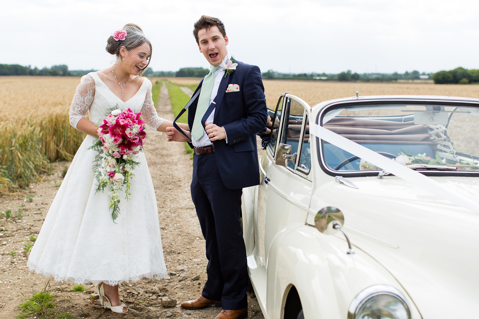 Yorkshire Wedding Photography Barn Venues bride and groom pose outside of vintage VW beetle