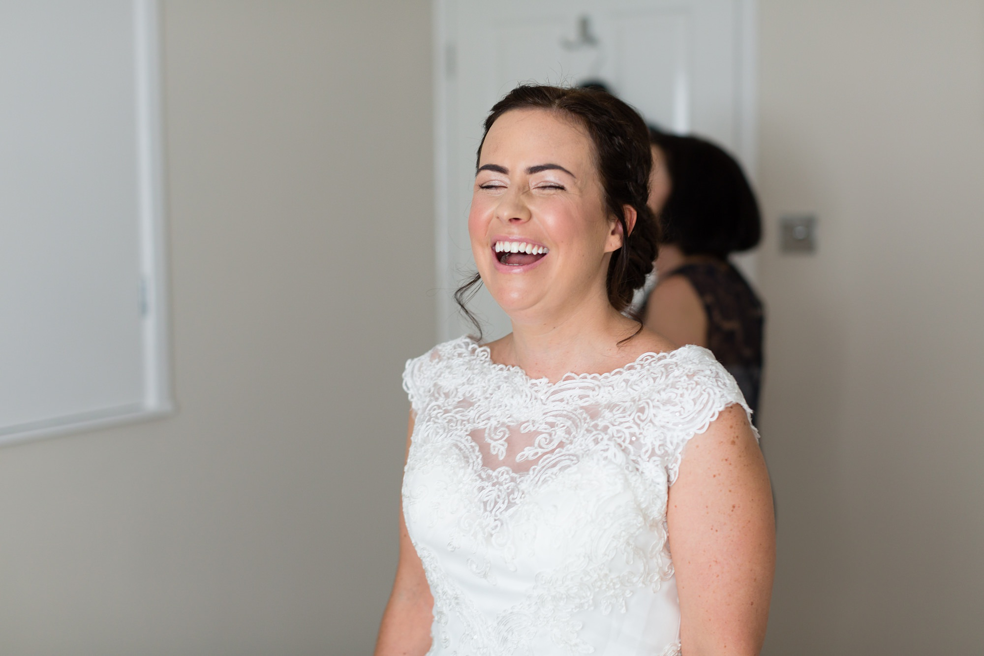 Bride laughing getting into dress.