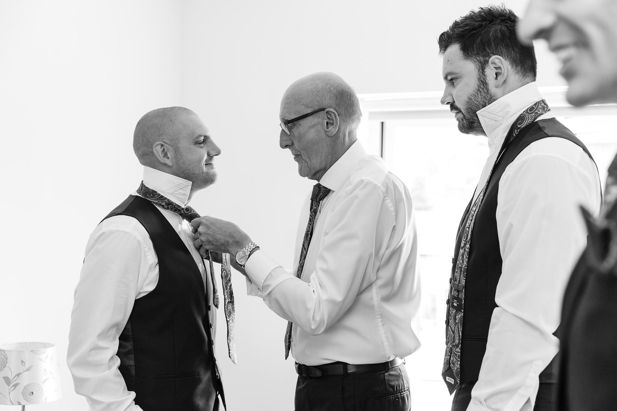 Groom prep ties being tied by dad