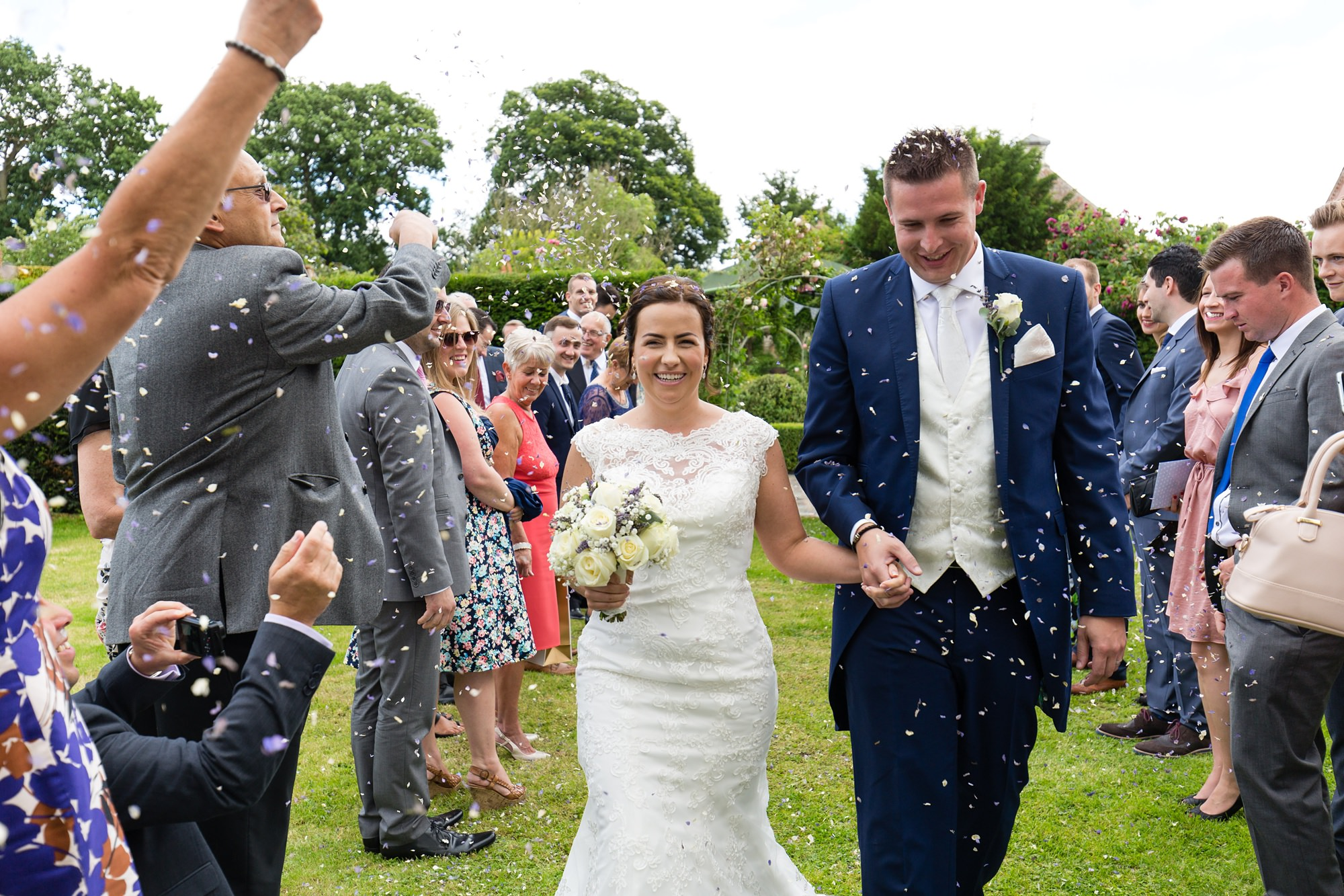 Bride and groom walk through confetti at Bell Hall
