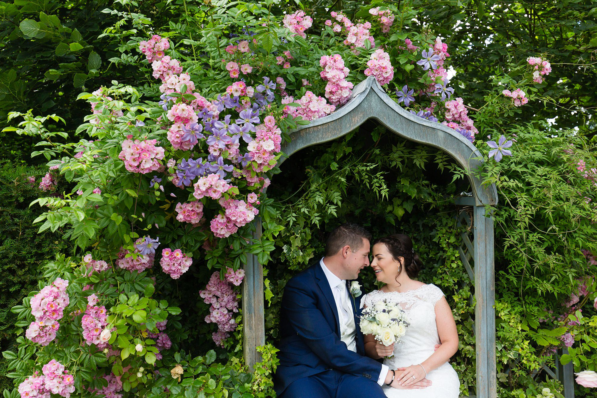 Bell Hall Wedding Photography brid eand groom cuddling in garden seat surrounded by hydrangeas
