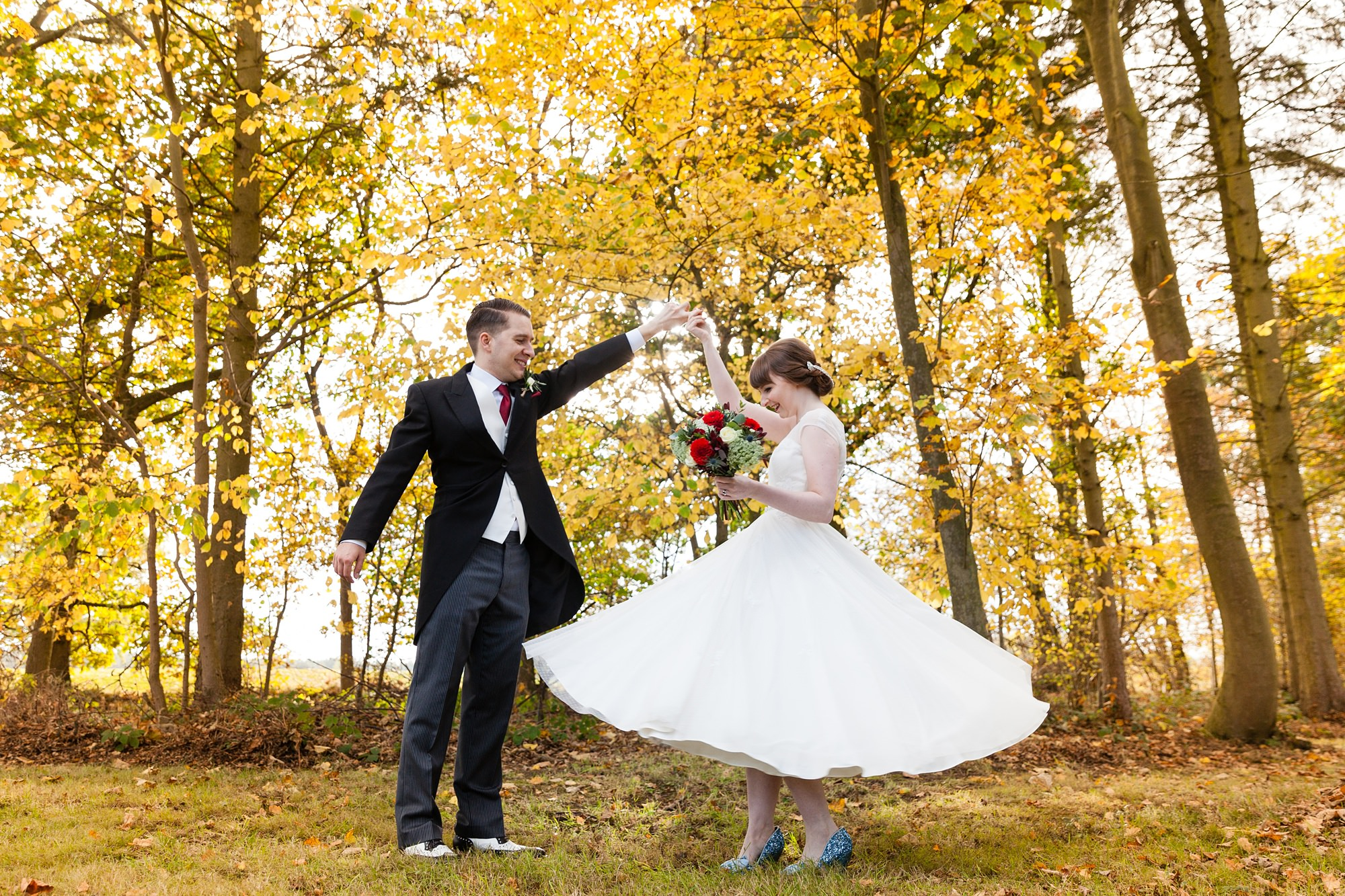 Groom twirls bride in yellow leaves Sandburn Hall Wedding Photography