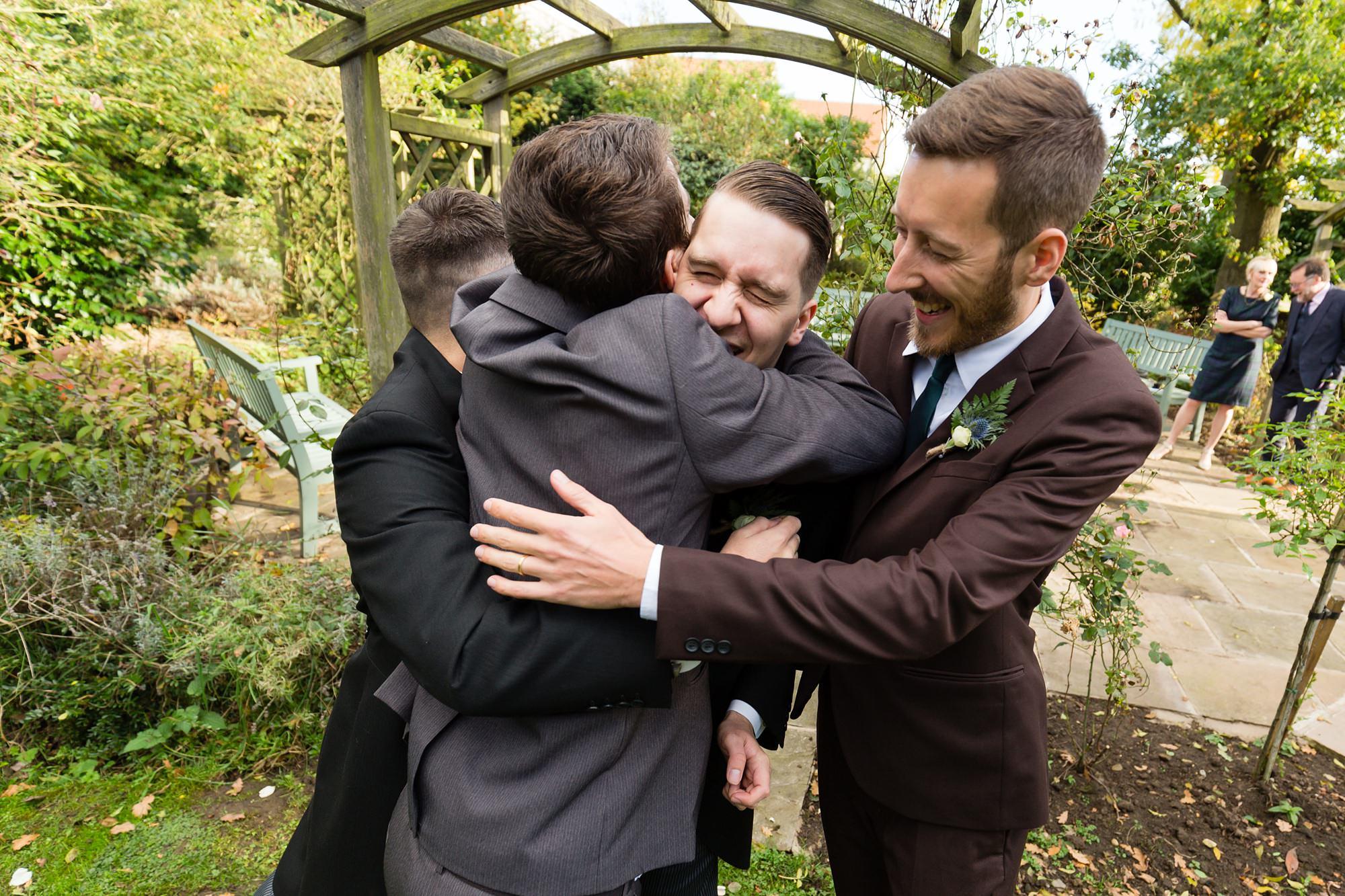 Groomsmen hug groom making him laugh Sandburn Hall Wedding Photography