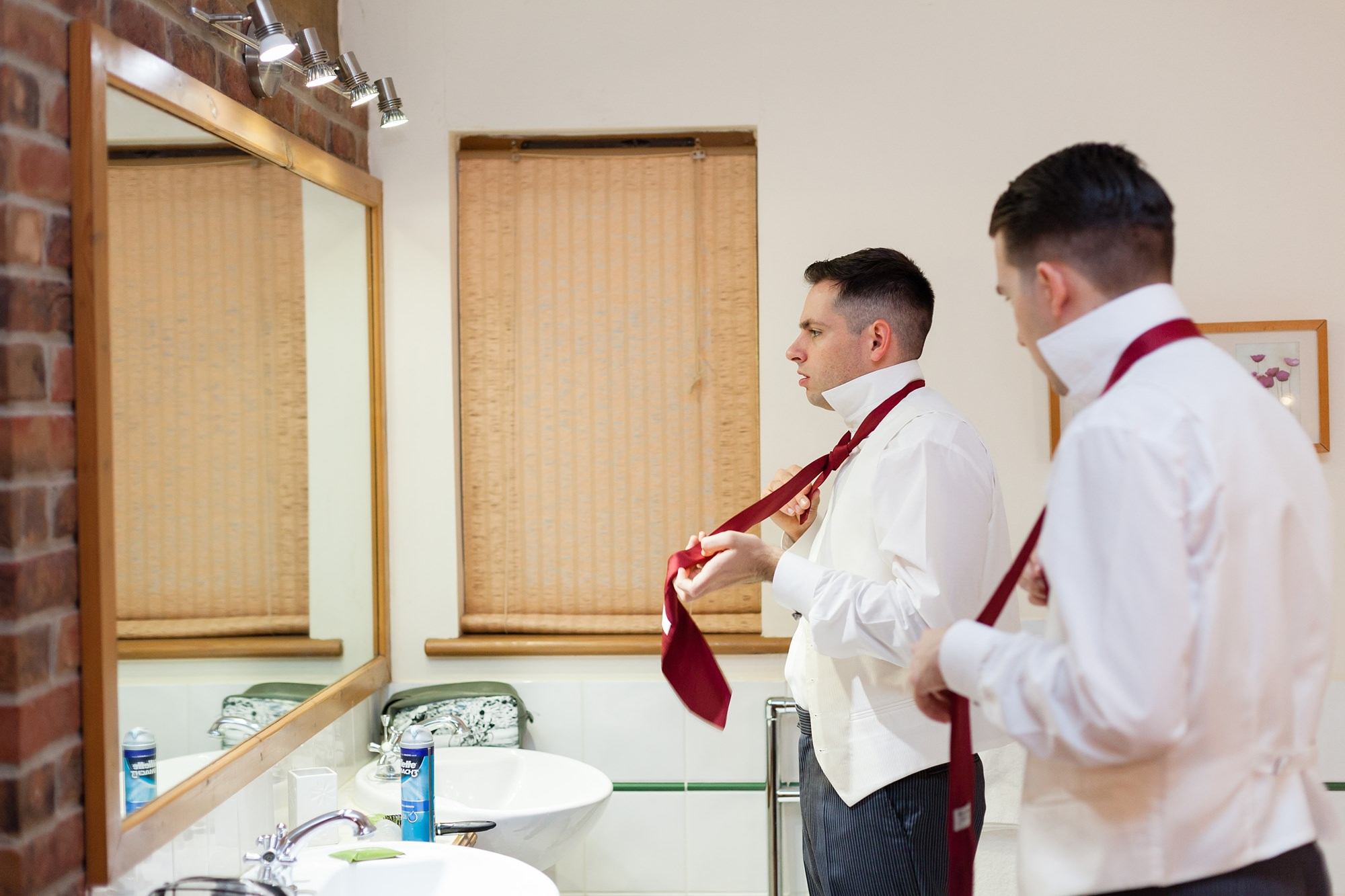 Yorkshire Wedding Photography groom and best man tyring up ties
