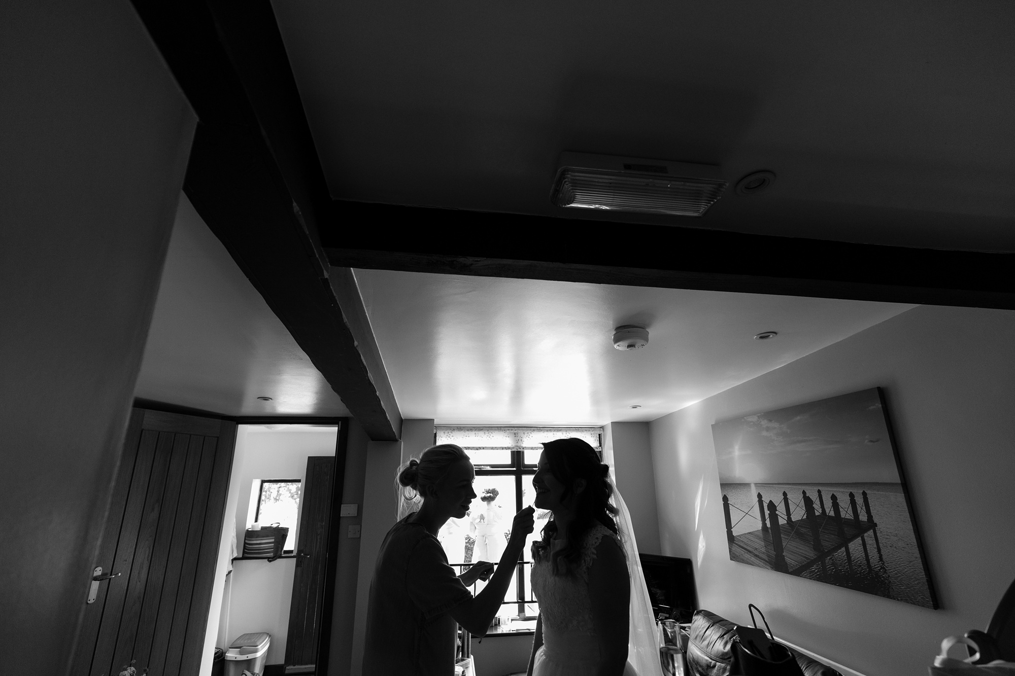 Silhouette of bride having makeup put on