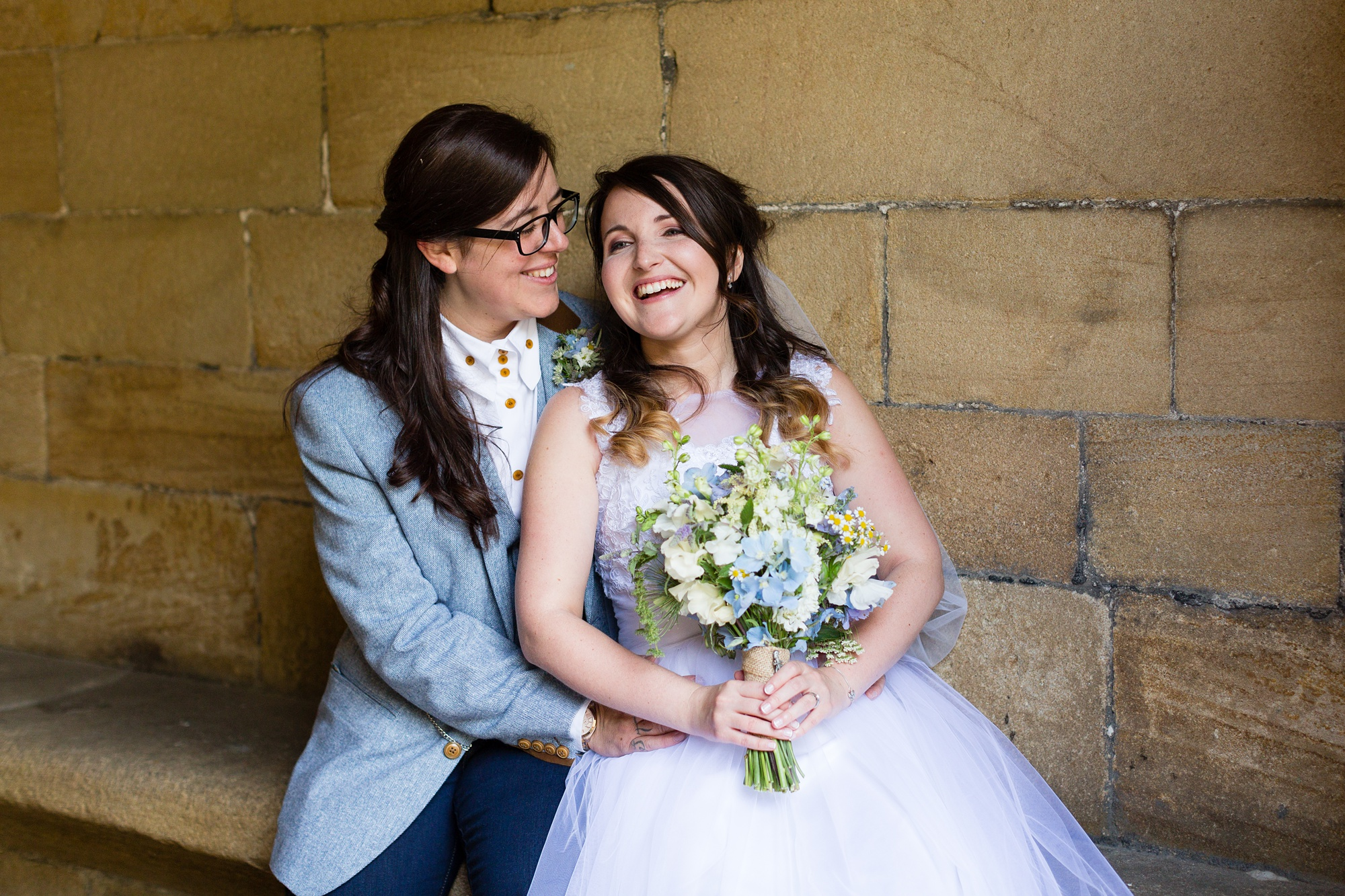 Brides cudding in archway East Riddlesden Hall Wedding Photography