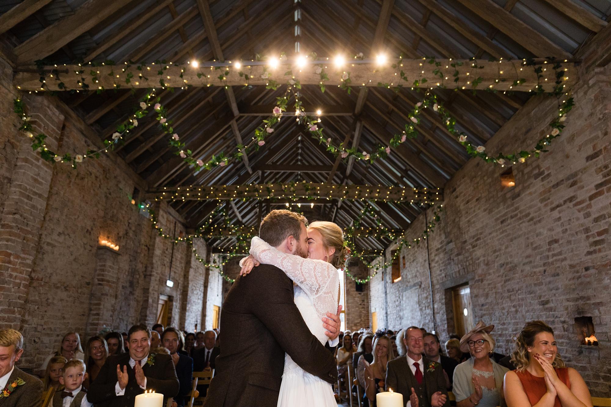 Yorkshire Wedding Photographers at Barmbyfield Barn big first kiss under fairy lights