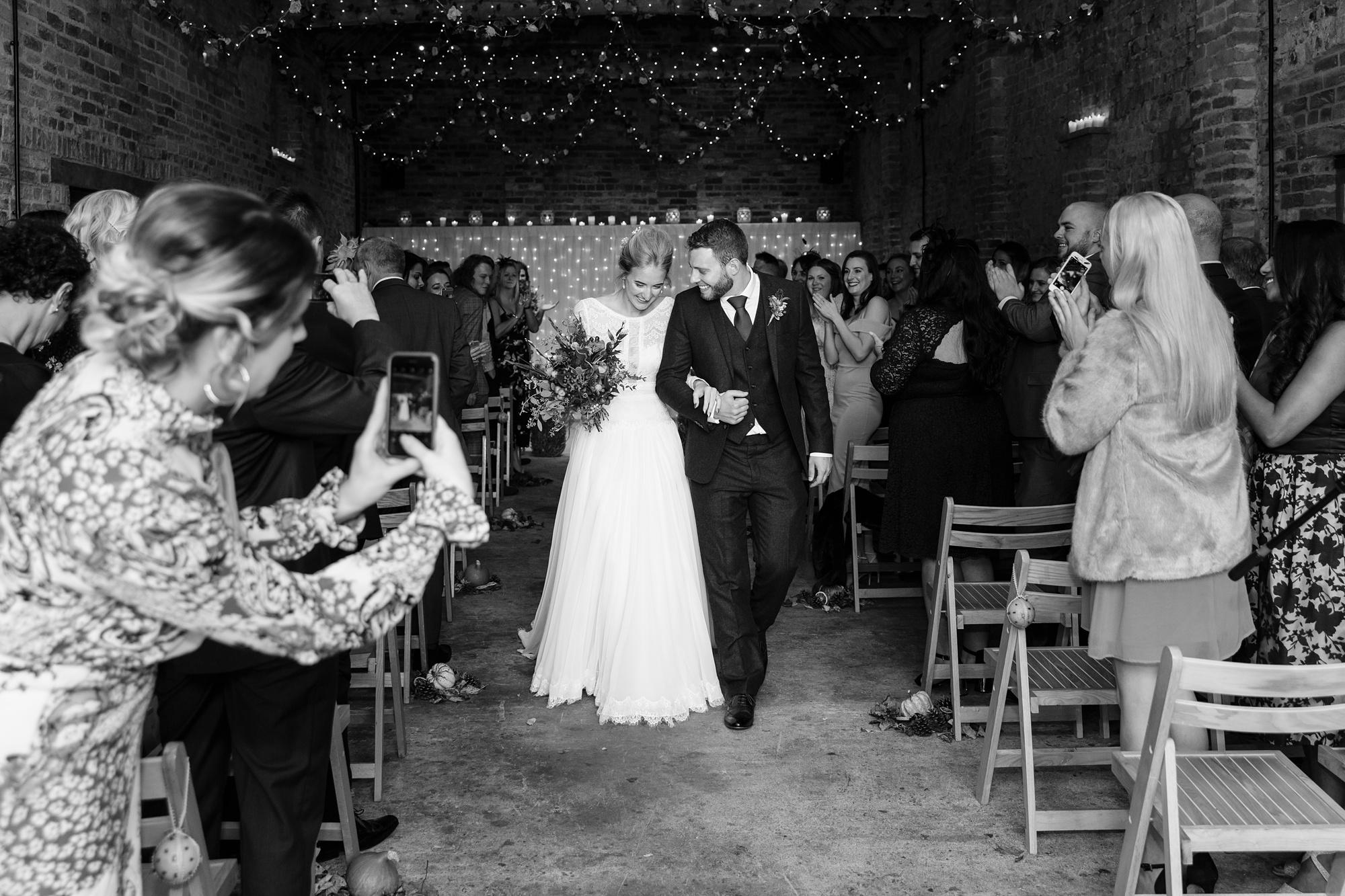 Yorkshire Wedding Photographers at Barmbyfield Barn walking back up the aisle