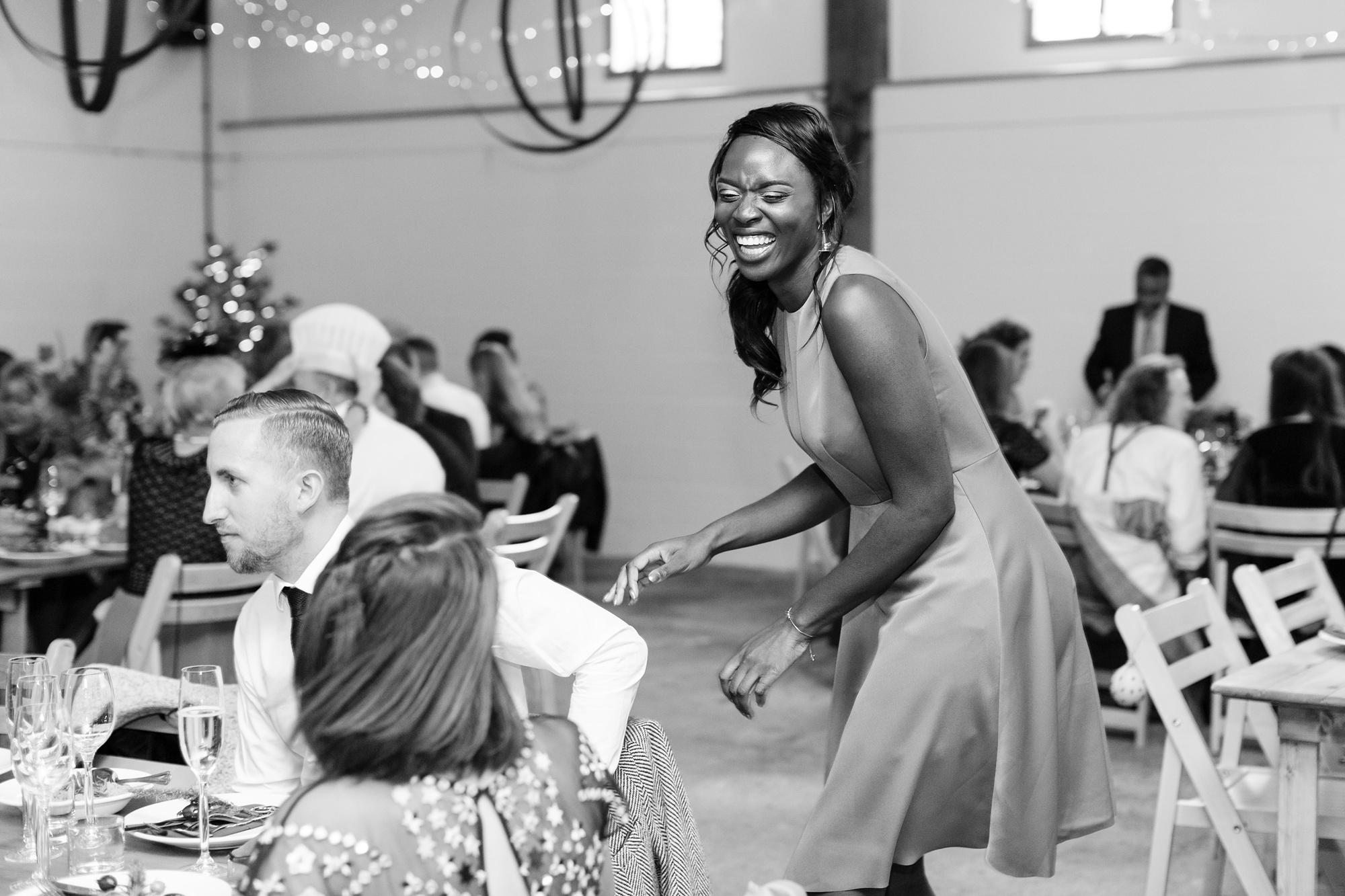 Bridesmaid laughing as she walks between tables Barmbyfield Barn Wedding Photography