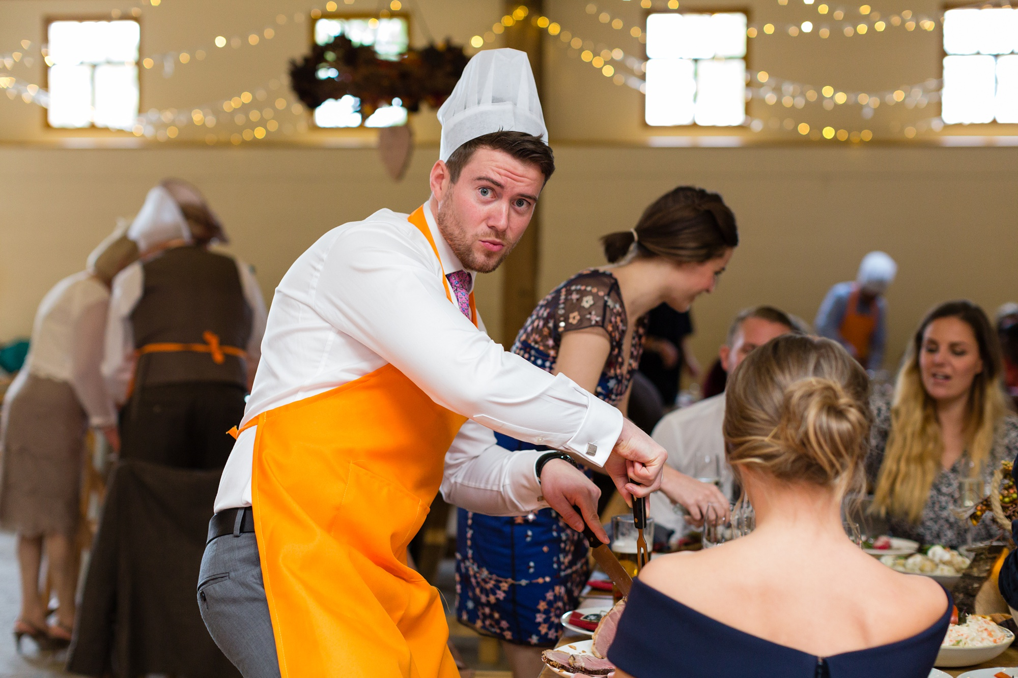 Yorkshire Wedding Photographers at Barmbyfield Barn guest makes funny face whilst carving meat