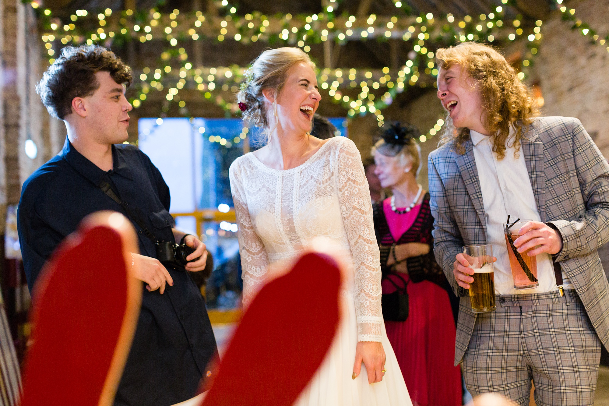 Bride laughs with friends and family Barmbyfield Barn Wedding Photography
