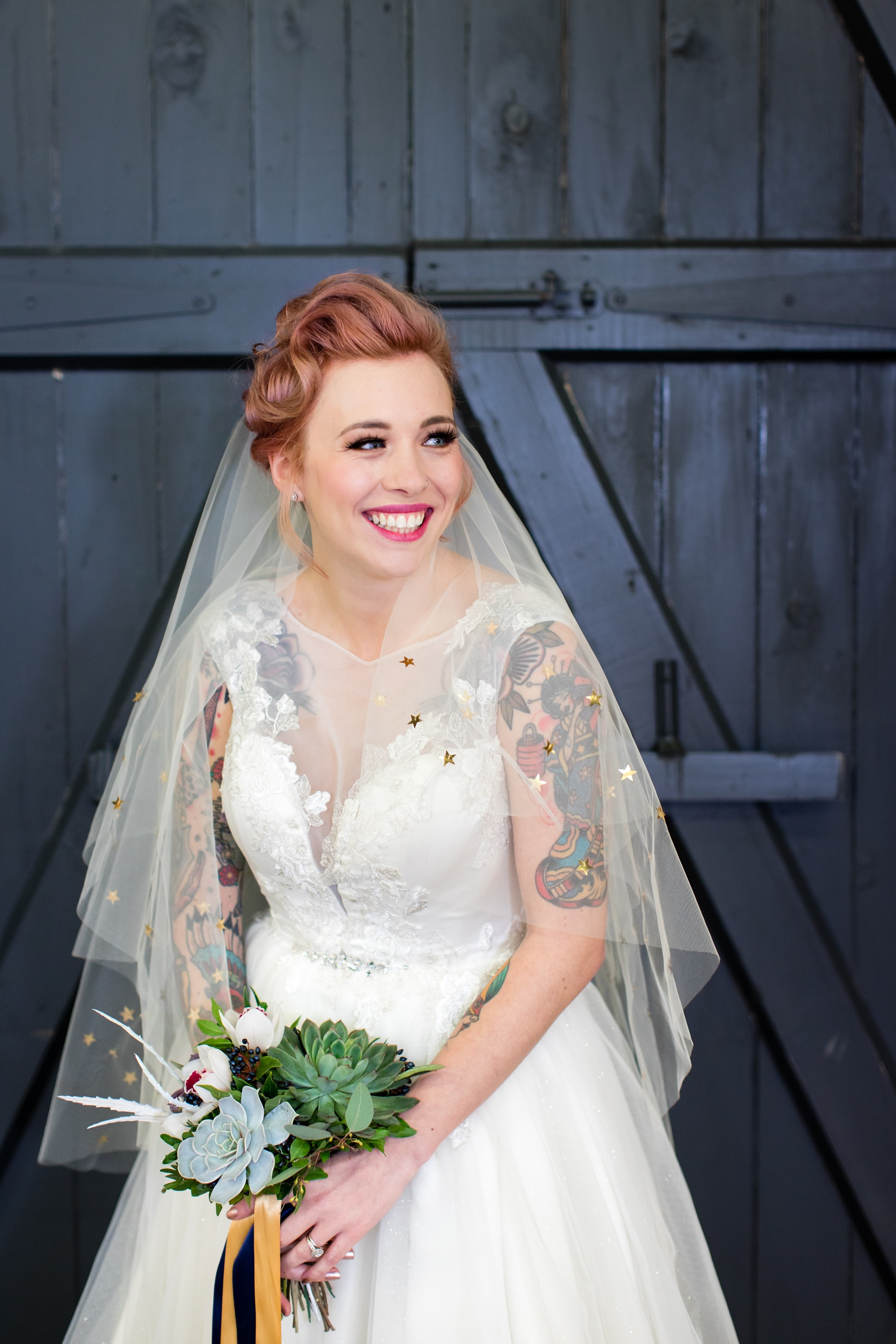 River Mills Ballroom Wedding Photography Tattooed bride wearing dress from Legend Bridal in front of grey blue door