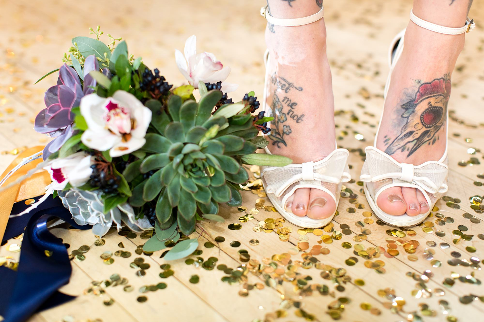White wedding shoes and bouquet standing on top of confetti on ballroom floor