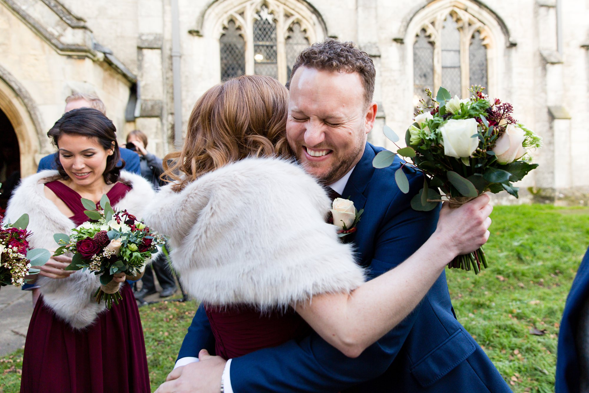 Groom hugs bridesmaid outside of church