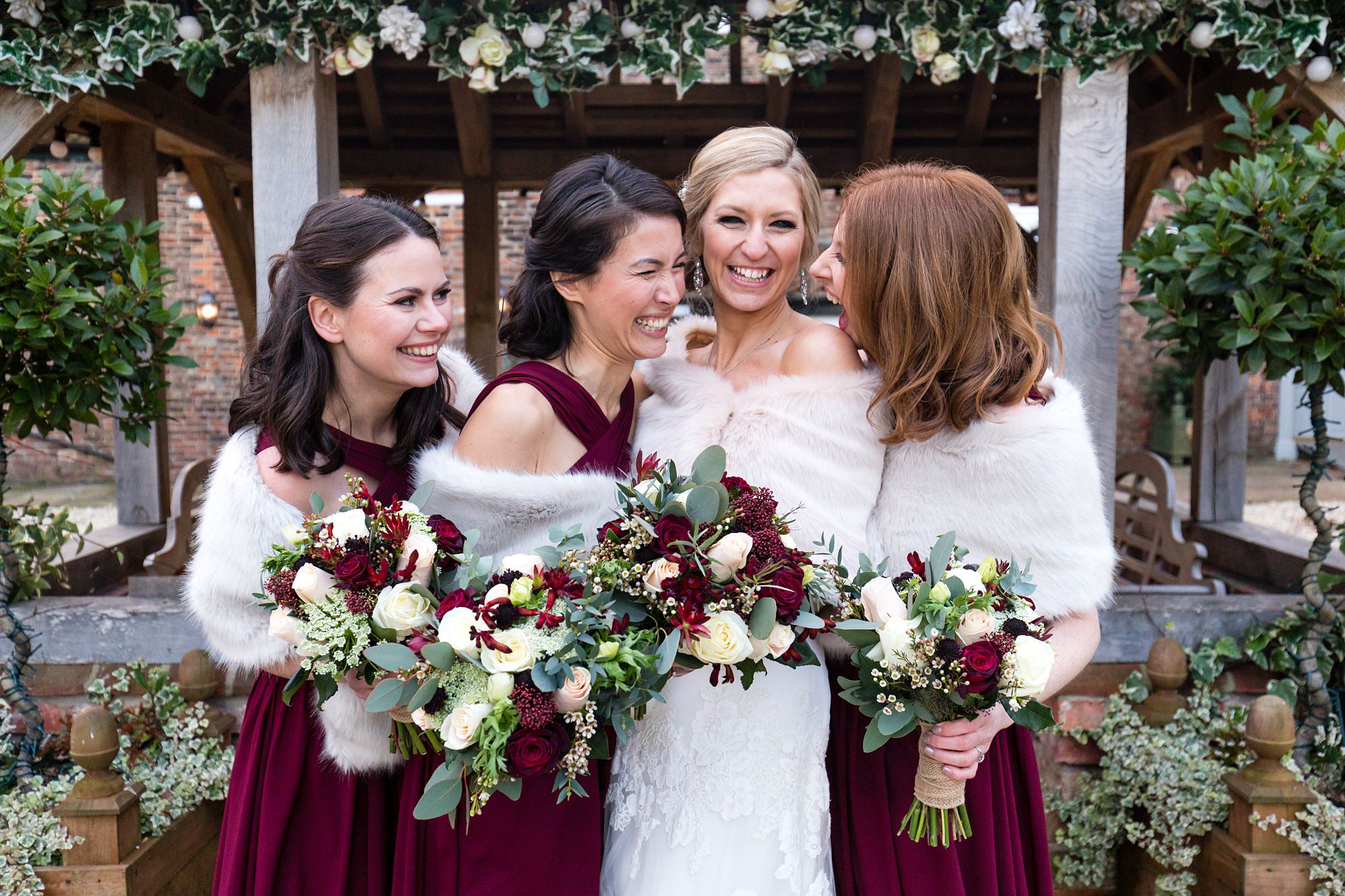 Bride Hugs bridesmaids outside of Lych Gates at Hornington Manor Farm