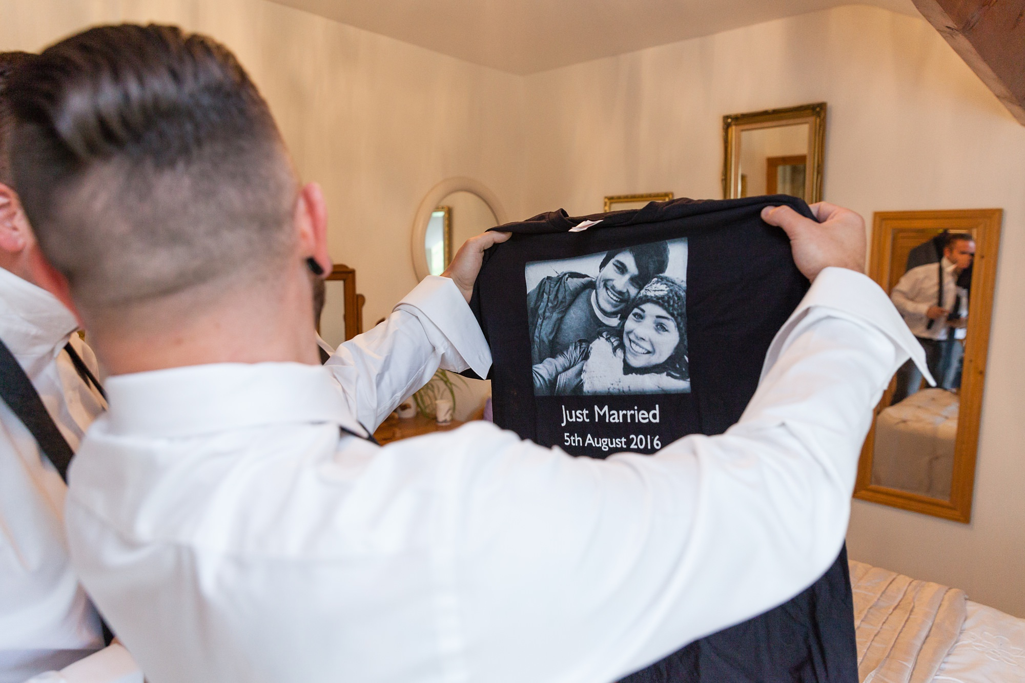 Groom looks at t-shirt made with their photo on it.