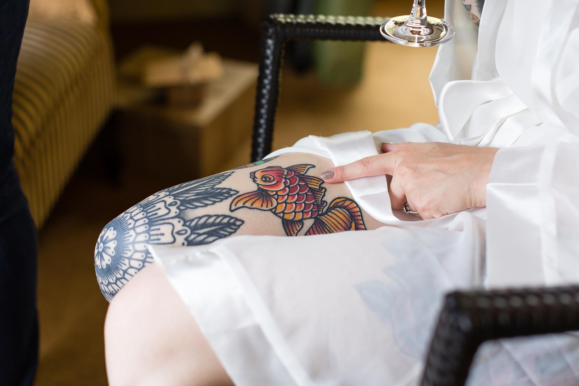 Tattooed bride shows leg tattoo