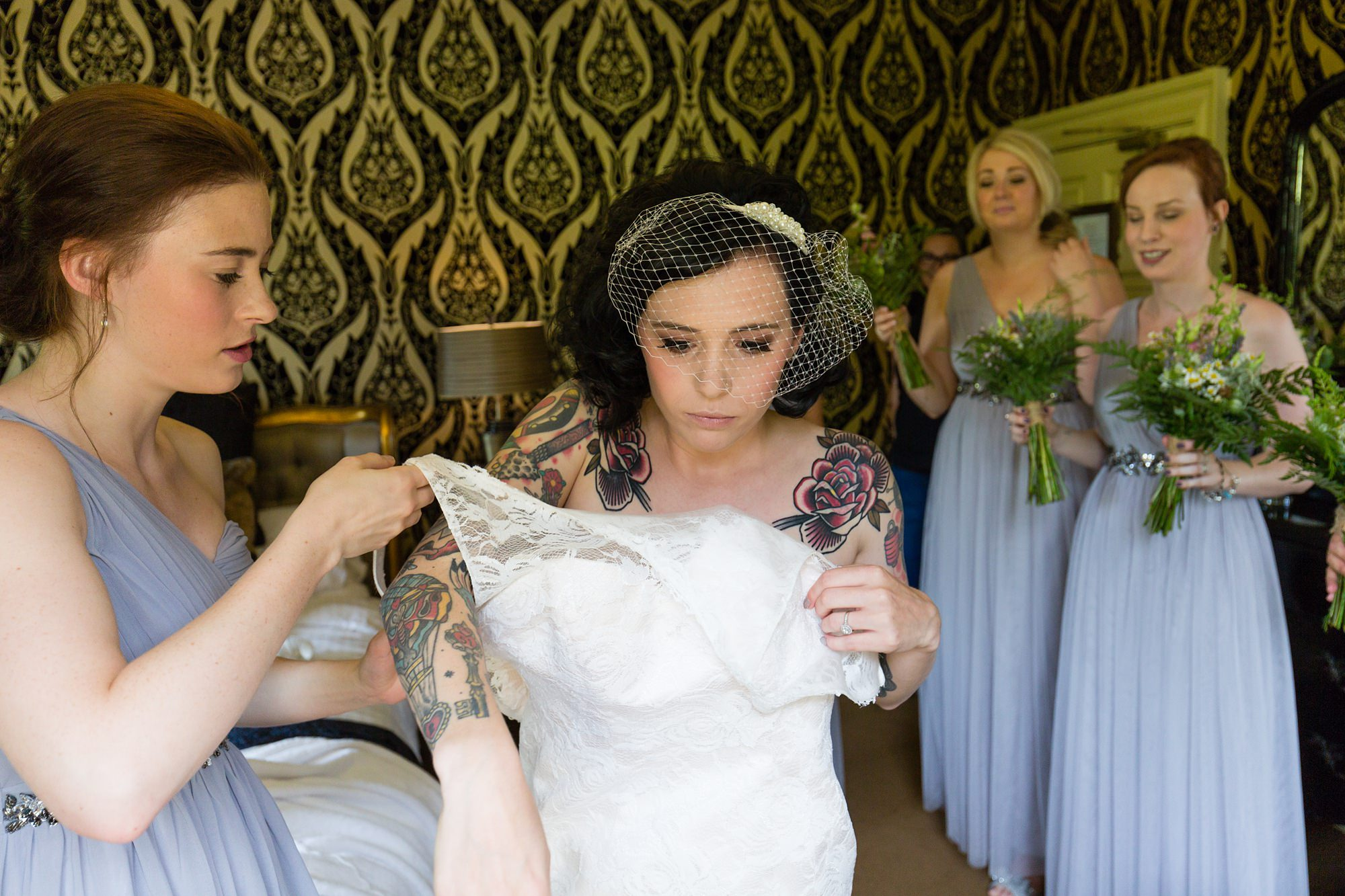 Bride gets into dress with tattoos on her shoulders