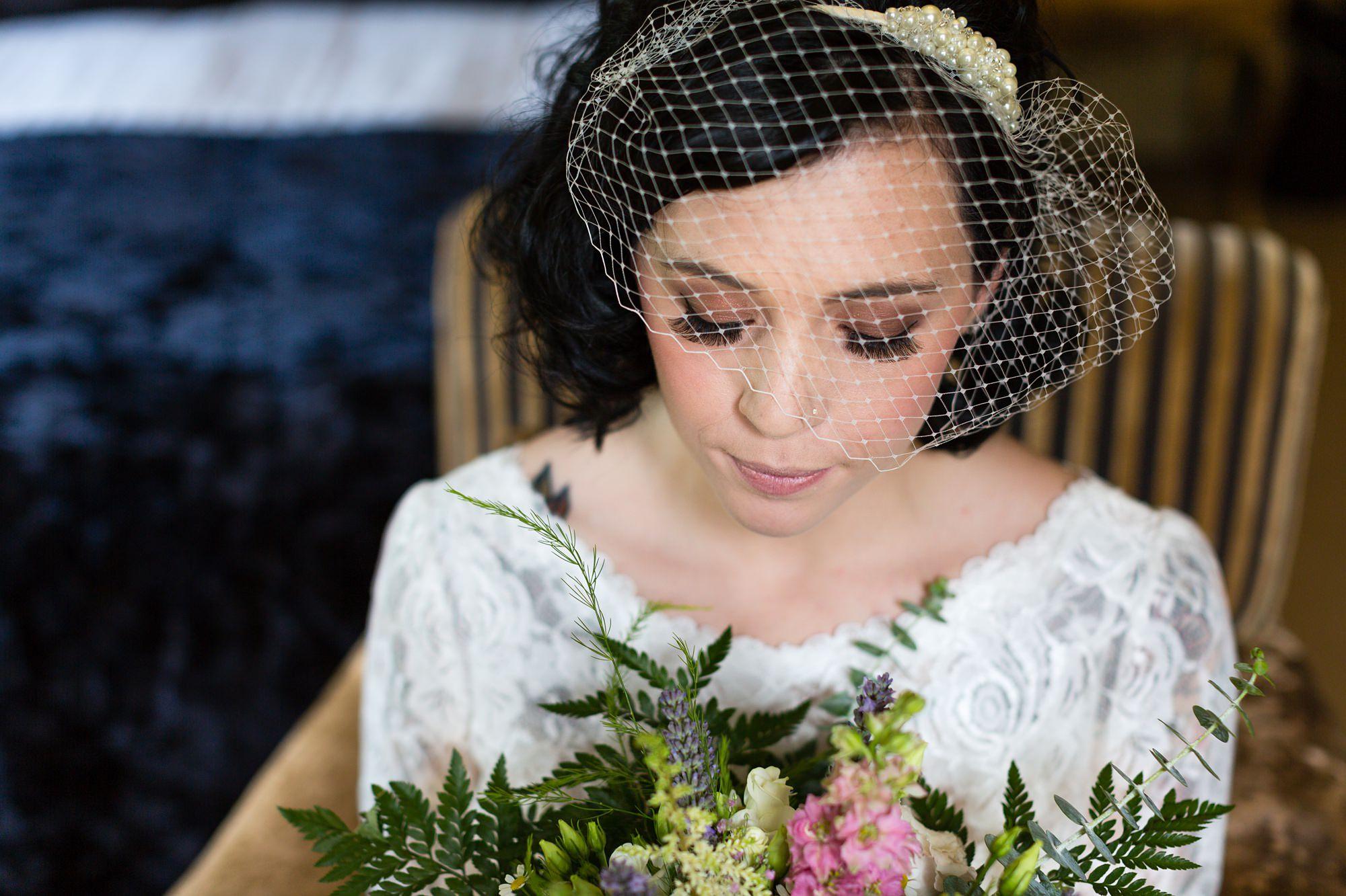 Bride looks down at bouquet