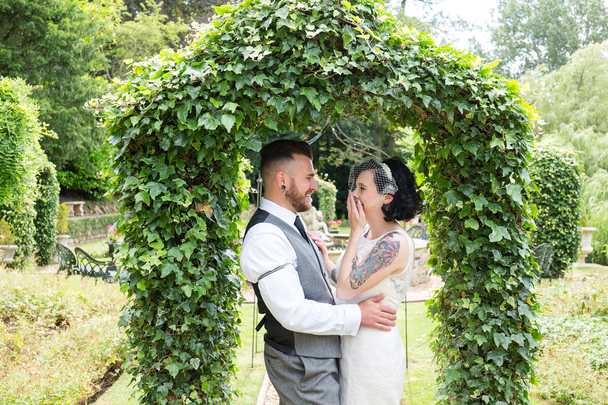 Tattooed wedding couple under the arch of ivy at Crab & Lobster