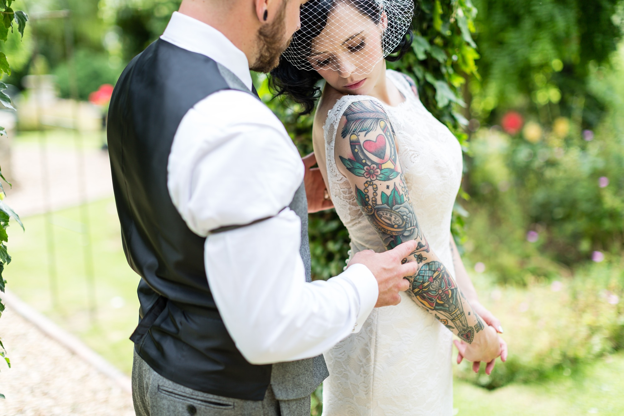 Groom looks at bride's tattooes at Crab & Lobster wedding