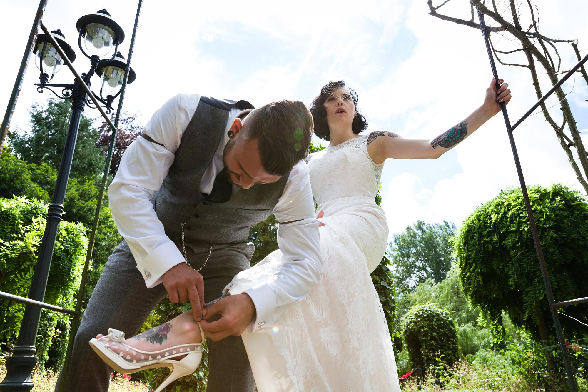 Groom helps bride fasten her shoe