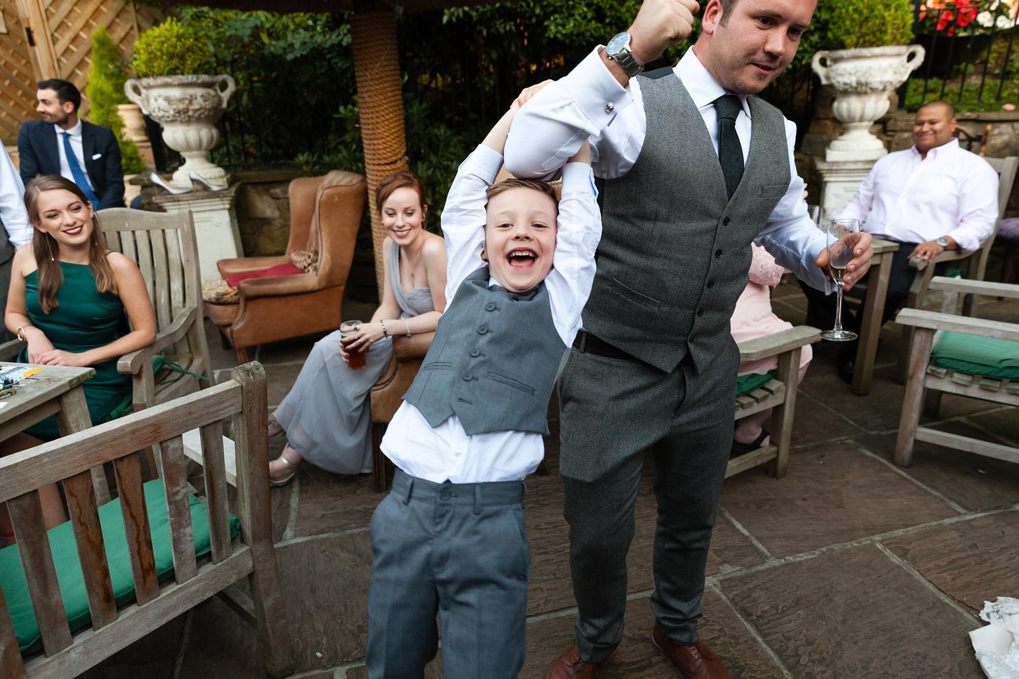 Child swinging around on groomsman's arm at Crab & Lobster wedding