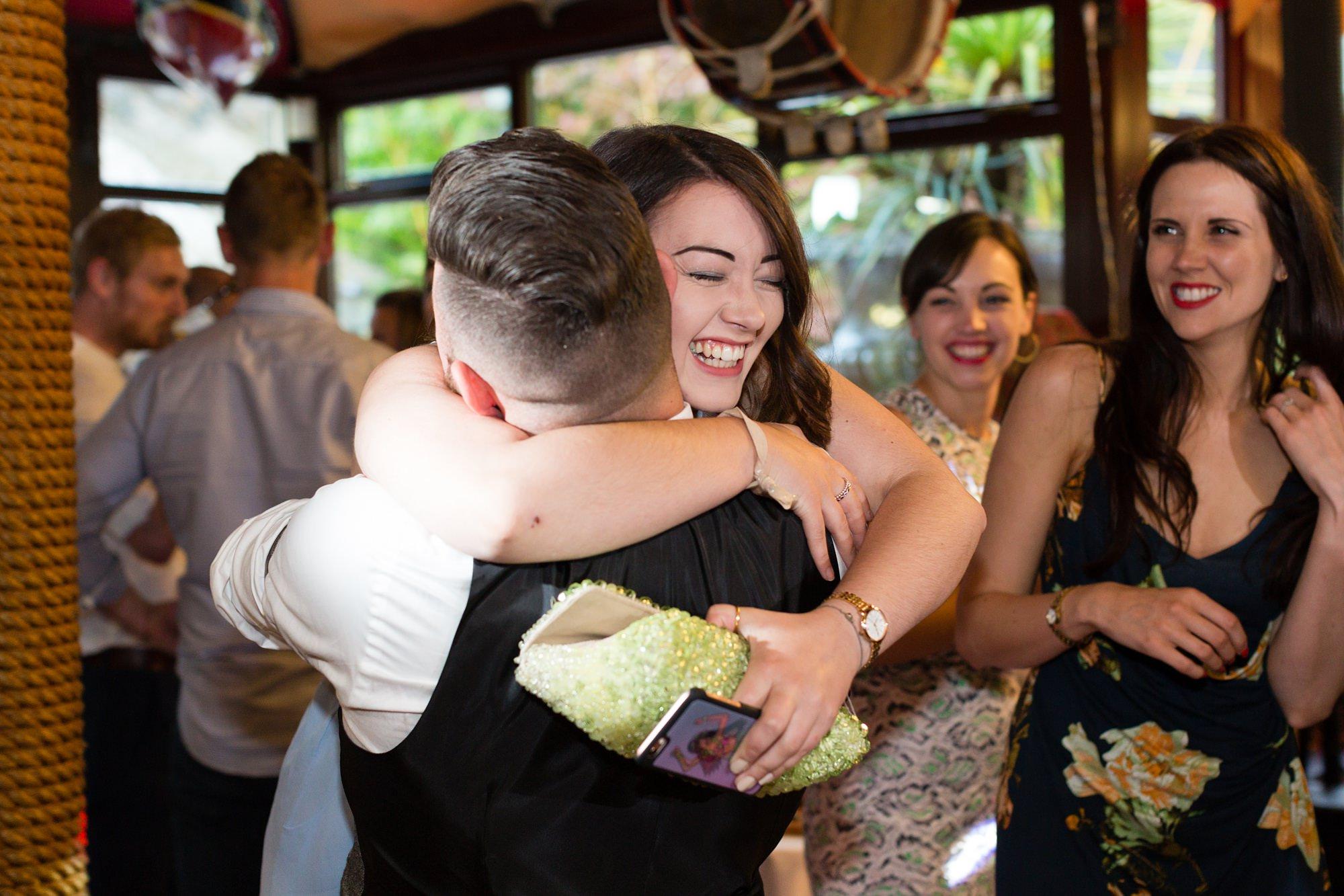 Guest hugging groom at Crab & Lobster wedding