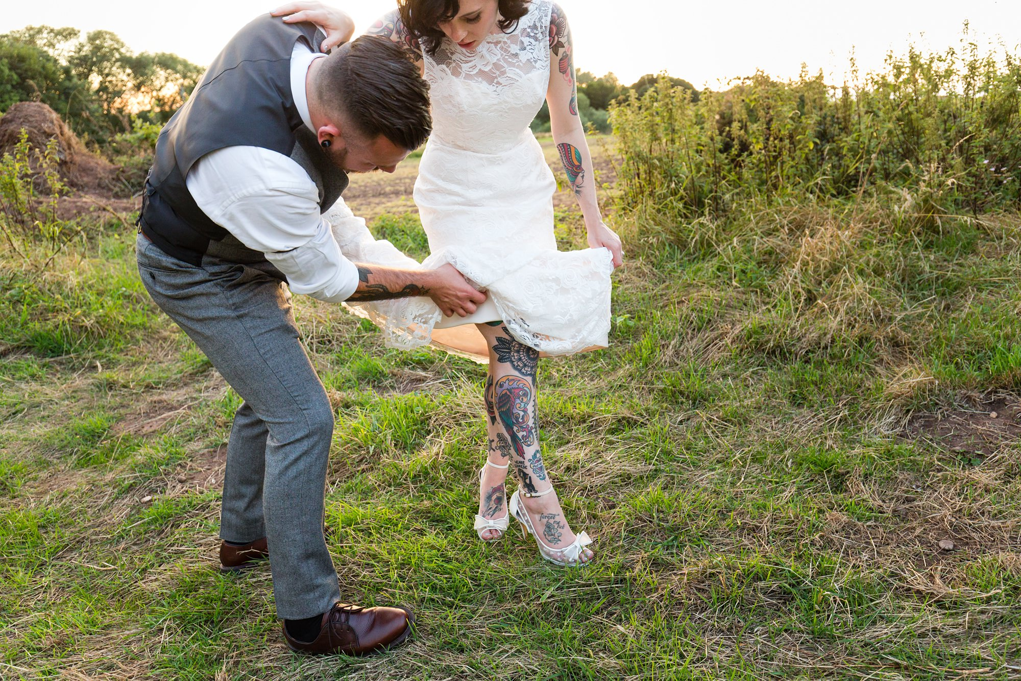Tattooed groom helps bride sort out her dress tattooed legs