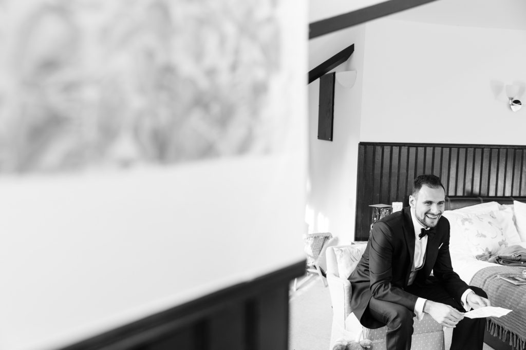 Black and white photograph of groom reading over his speech in the morning before wedding at Achnagairn Estate