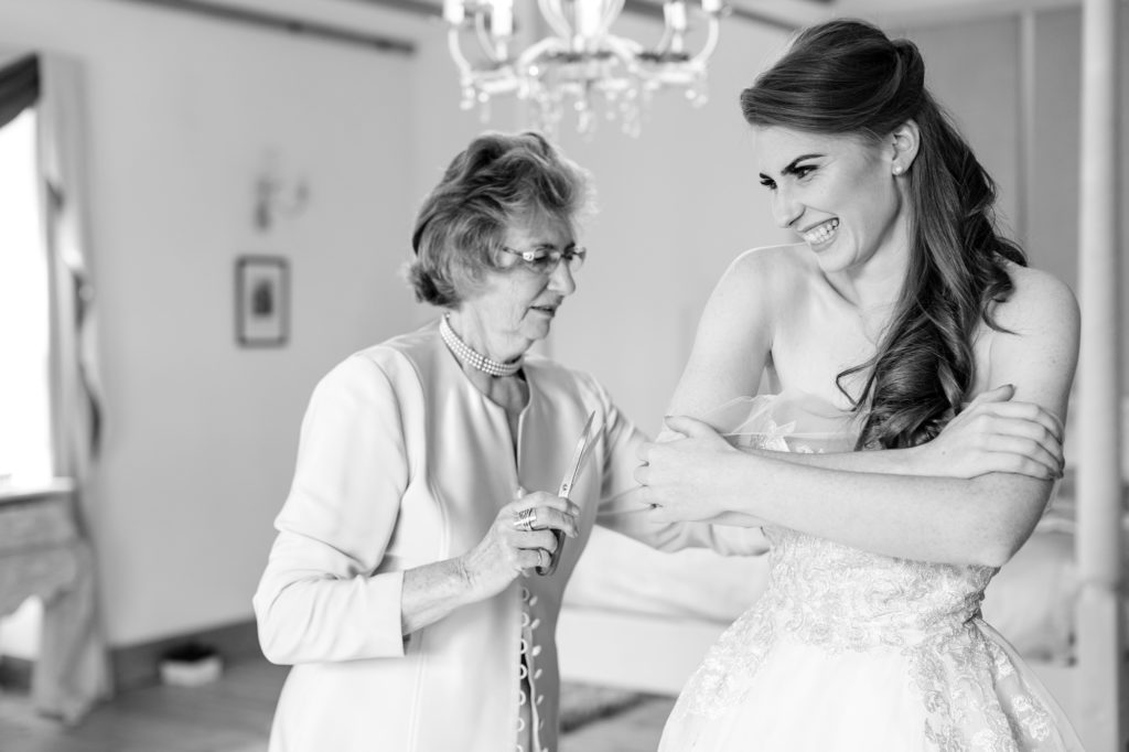 Bride's grandmother helps her into her dress in black and white wedding photograph