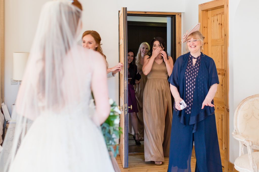Bride's mother and bridesmaids seeing her for the first time.