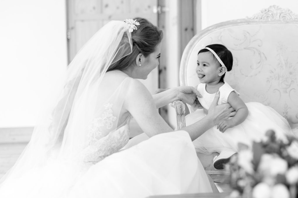 Bride having a sweet moment with little flower girl who is sticking out her tongue.