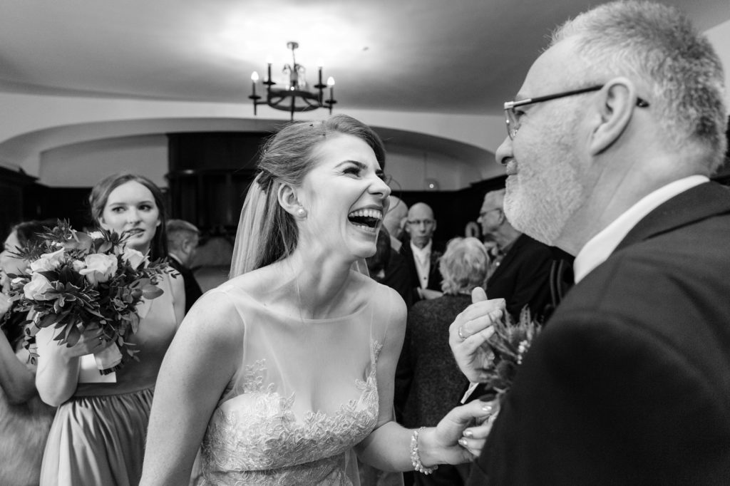 Bride laughs and smiles with guests at Achnagairn Estate wedding candid