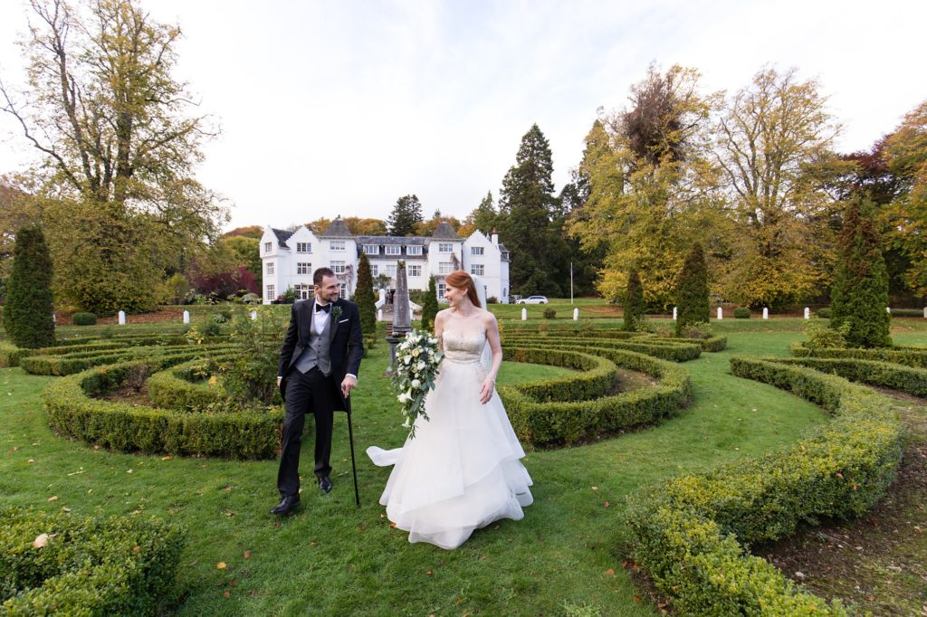 Bride and groom walk through autumn garden maze at Achnagairn Estate