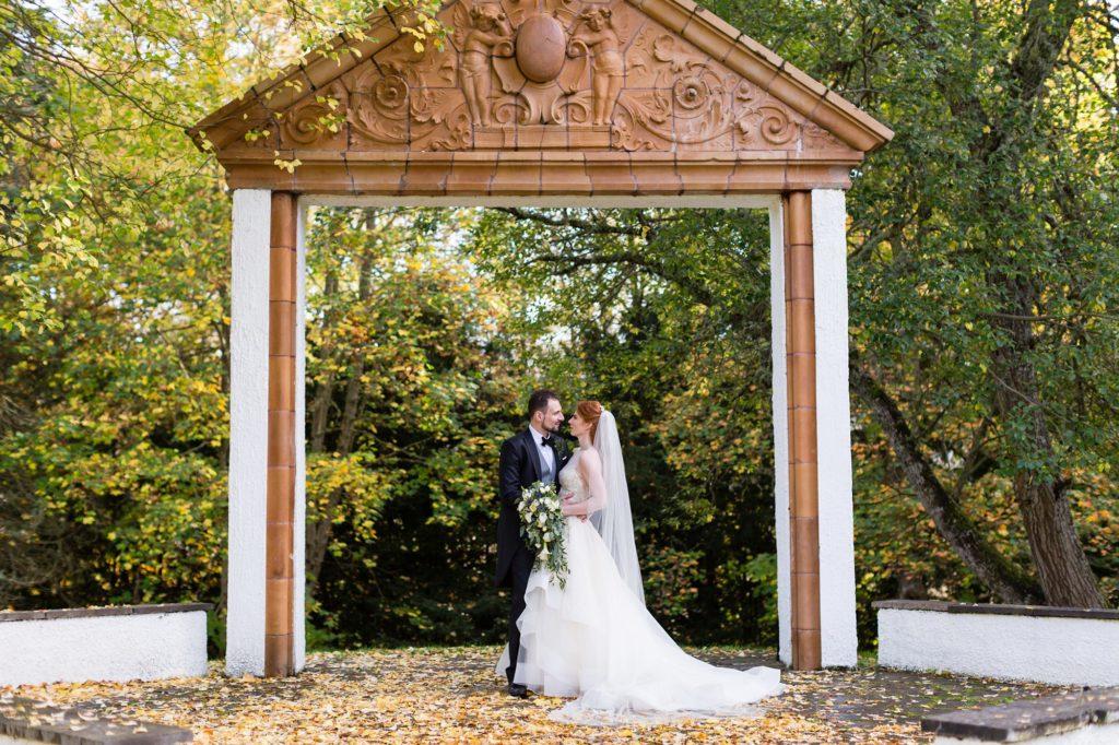 Bride & groom under folly at Achnagairn Estate