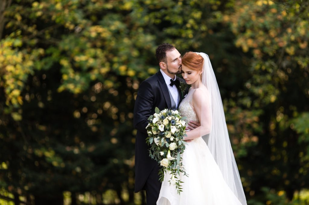 Groom kisses forehead of redheaded bride at Achnagairn Estate
