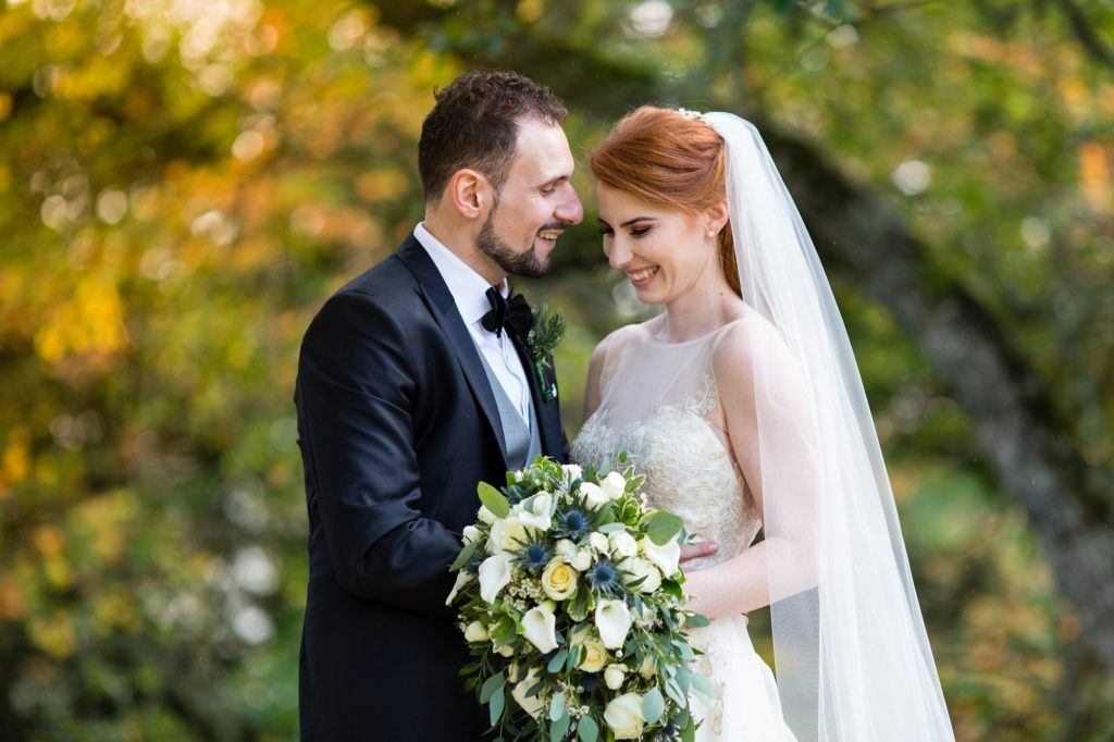 Bride & groom laugh and smile in autumn wedding photograph