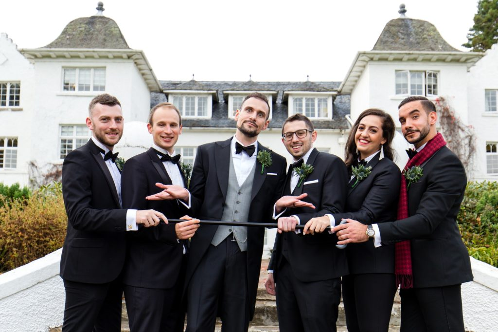 Groom makes silly face with cane with wedding party