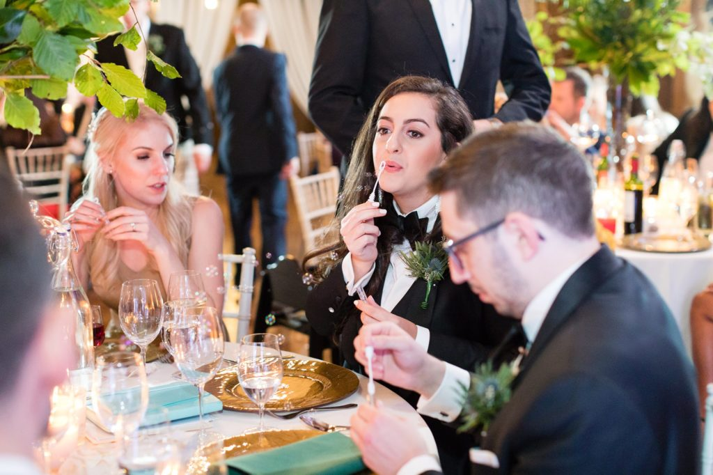 Groom'smaid blowing bubbles at a table.