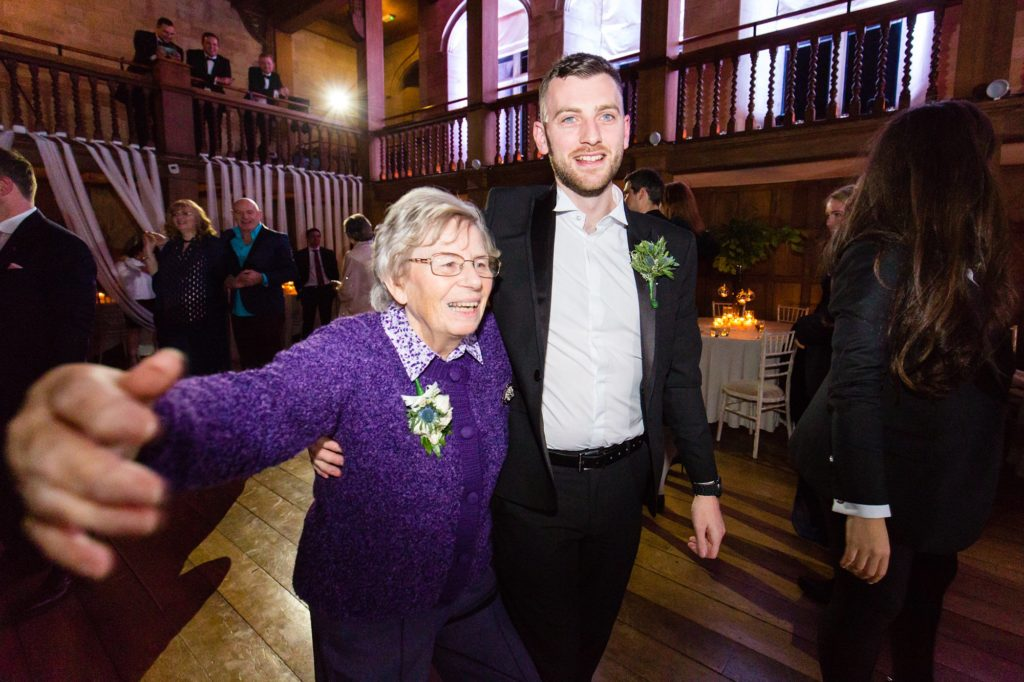 Grandmother dancing with groomsman at wedding.