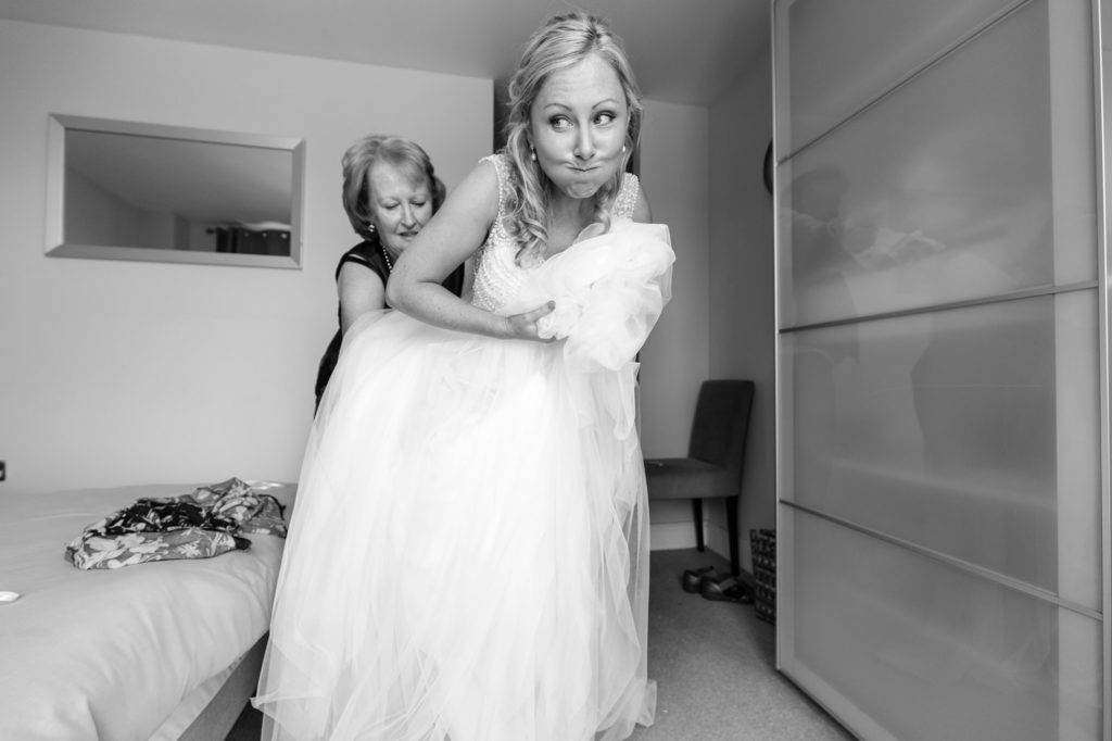 Bride makes hilarious face when putting on wedding dress.