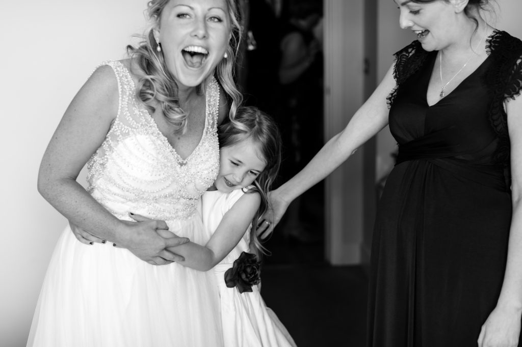 Bride smiles and hugs bridesmaid at Asylum wedding.