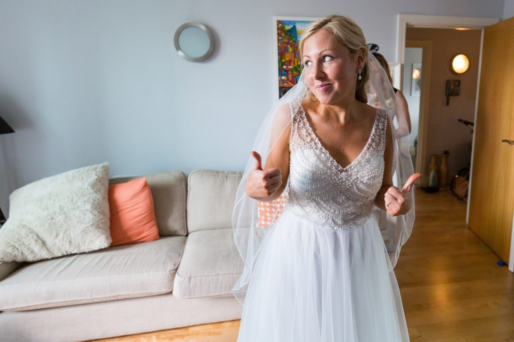 Bride gives thumbs up in beaded wedding dress.