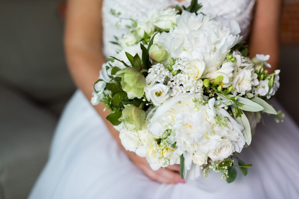 Bride holds all-white wedding bouquet with peonies at Asylum wedding.