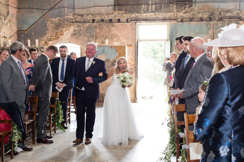 Bride makes happy face as she walks up aisle at Asylum wedding venue.